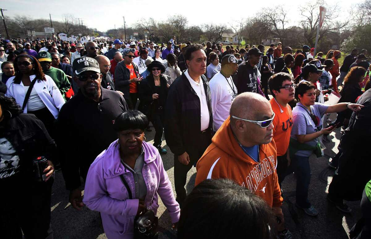 Former San Antonio Mayor Henry Cisneros, center marches in the Martin Luther King, Jr. March along MLK Blvd. Jan. 21, 2013.