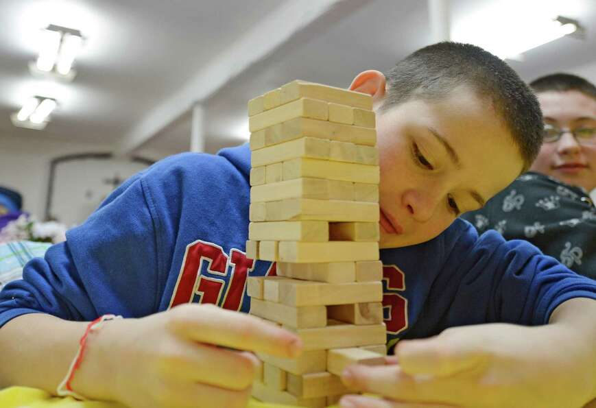 David Genier, 13, plays Jenga on Martin Luther King Jr. Day on Jan. 21, 2013, at the Missing Link St