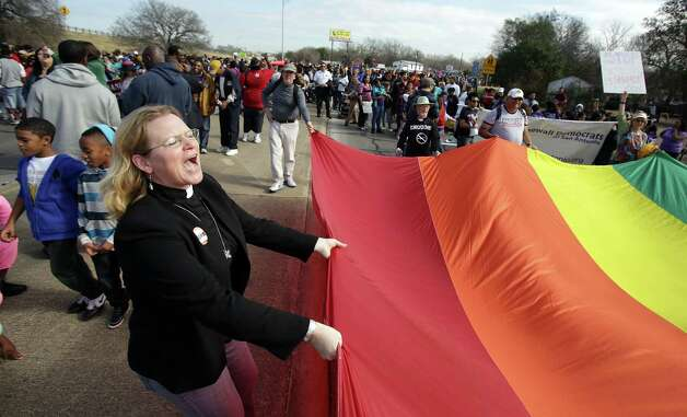 Rev. Gusti Newquist, of Madison Square Presbyterian Chursh carries a section of a rainbow flag during the Martin Luther King, Jr. March along MLK Blvd.  Jan. 21, 2013. Photo: BOB OWEN, San Antonio Express-News / © 2012 San Antonio Express-News