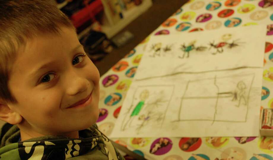 Parker Teed, 7, displays his artistic creation at a Westport Historical Society workshop Monday, which was inspired by some of the messages of Martin Luther King Jr.  WESTPORT NEWS, CT 1/21/13 Photo: Jarret Liotta / Westport News contributed