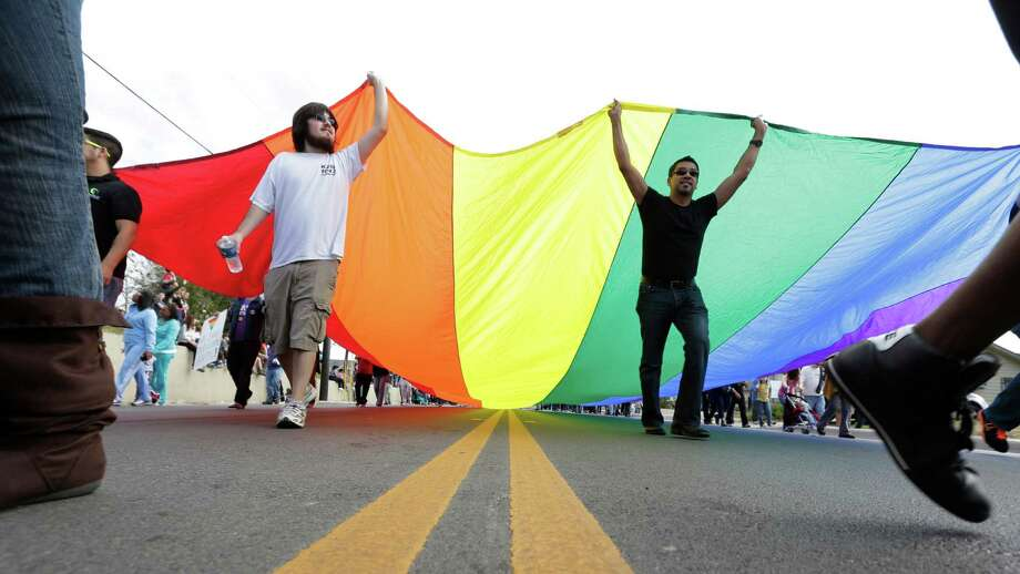 A group carries a rainbow flag as they take part in a march honoring Martin Luther King Jr., Monday, Jan. 21, 2013, in San Antonio. (AP Photo/Eric Gay) Photo: Eric Gay, Associated Press / AP
