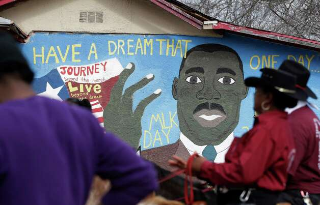 Riders pass a mural as they take part in an MLK Day march honoring Martin Luther King Jr., Monday, Jan. 21, 2013, in San Antonio. (AP Photo/Eric Gay) Photo: Eric Gay, Associated Press / AP
