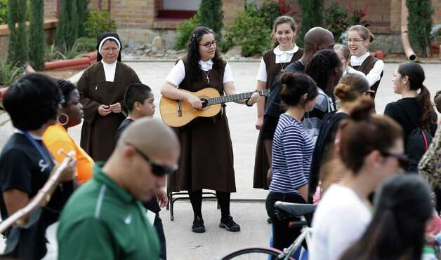 Nuns sing as participants in an MLK Day march honoring Martin Luther King Jr. pass by, Monday, Jan. 21, 2013, in San Antonio. (AP Photo/Eric Gay) Photo: Eric Gay, Associated Press / AP