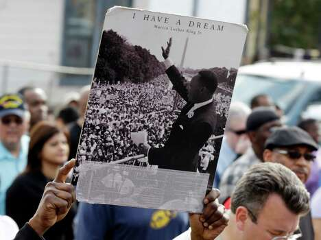 A man carries a photo of Martin Luther King Jr. during a MLK Day march honoring Martin Luther King Jr., Monday, Jan. 21, 2013, in San Antonio. (AP Photo/Eric Gay) Photo: Eric Gay, Associated Press / AP