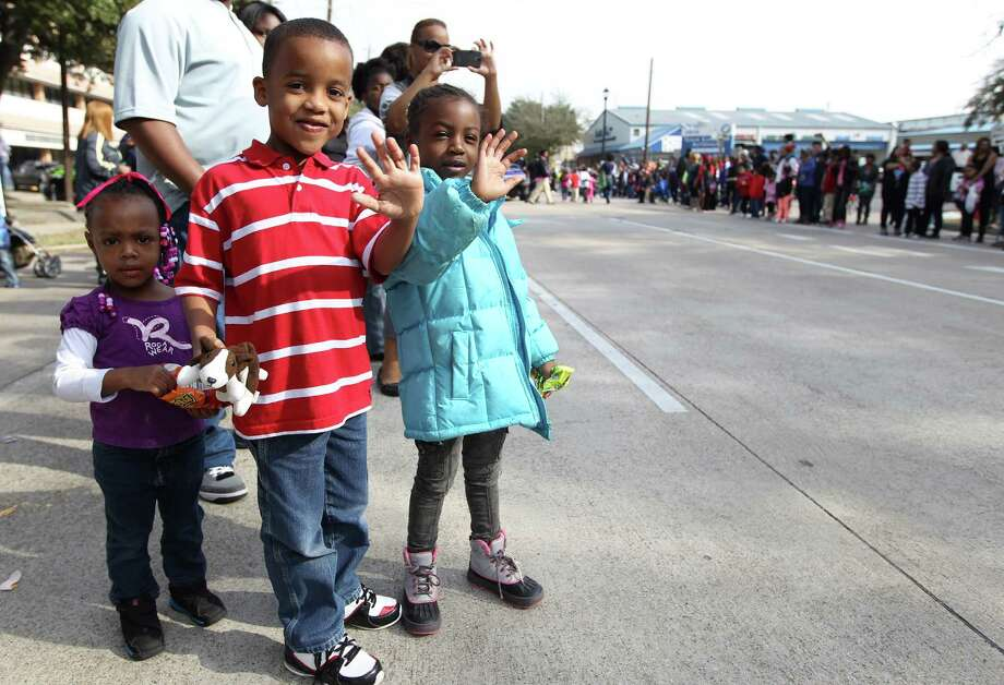 Ariya Keezie, 2, with Noel Walker, 6, and Jalaysia Keezie, 5, wave at the participants marching by during the 19th Annual MLK Grande Parade by the MLK Parade Foundation, which started on San Jacinto and Rosalie Streets in Midtown, Monday, Jan. 21, 2013. Photo: Karen Warren, Houston Chronicle / © 2013 Houston Chronicle