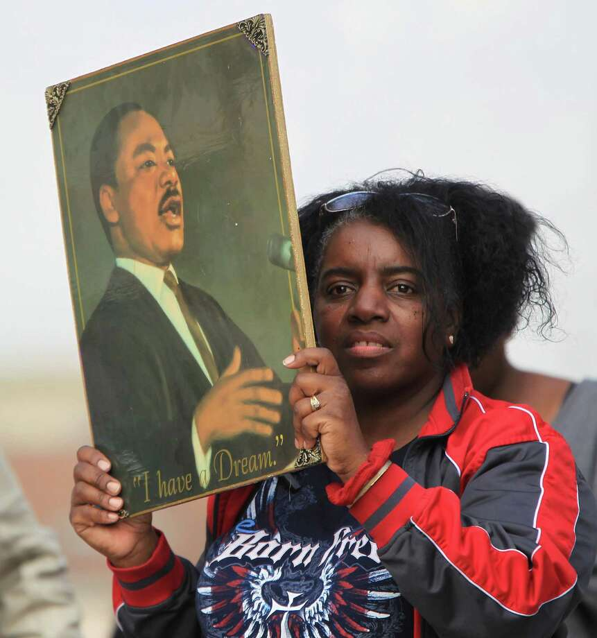 Marilyn Smith holds up a painting done by her godson of Rev. Martin Luther King during the 19th Annual MLK Grande Parade by the MLK Parade Foundation, which started on San Jacinto and Rosalie Streets in Midtown, Monday, Jan. 21, 2013. Photo: Karen Warren, Houston Chronicle / © 2013 Houston Chronicle