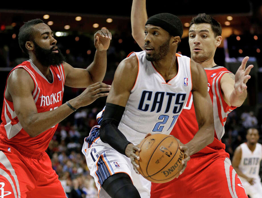Bobcats forward Hakim Warrick, center, looks to pass as he is trapped by Rockets' Carlos Delfino, right, and James Harden, left, during the first half. Photo: Chuck Burton, Associated Press / AP