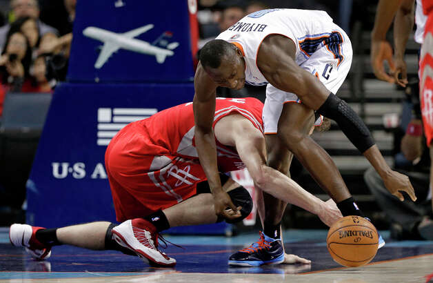 Bobcats forward Bismack Biyombo, top, and Rockets center Omer Asik, bottom, chase a loose ball during the first half. Photo: Chuck Burton, Associated Press / AP