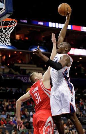 Bismack Biyombo, right, shoots over Cole Aldrich, left, during the first half. Photo: Chuck Burton, Associated Press / AP