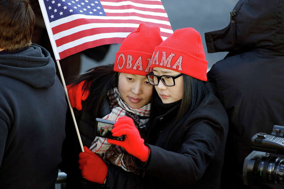 Khongorzul Battsengel, left, and Ariunbolor Davaatsogt both from Mongolia, take a picture of themselves as they wait for President Barack Obama in the 57th Presidential Inaugural Parade on Pennsylvania Avenue, Monday, Jan. 21, 2013 in Washington. Thousands marched during the 57th Presidential Inauguration parade after the ceremonial swearing-in of Obama. (AP Photo/Alex Brandon) Photo: Alex Brandon, ASSOCIATED PRESS / AP2013