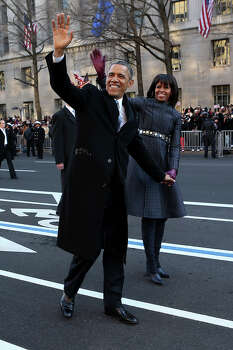 President Barack Obama and first lady Michelle Obama wave as they walk down Pennsylvania Avenue in Washington, Monday, Jan. 21, 2013, during the inaugural parade route , after his ceremonial swearing-in on Capitol Hill during the 57th Presidential Inauguration. Photo: Doug Mills, AP / Pool New York Times