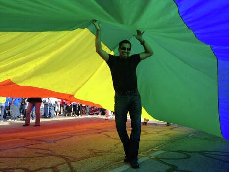 "Alvaro Duarte supports an oversized rainbow flag at the MLK march for the San Antonio chapter of the Human Rights Campaign ""as a part of the multicultural groups that make up our beautiful city."" Jan. 21. Photo: Sarah Tressler/Express-News"