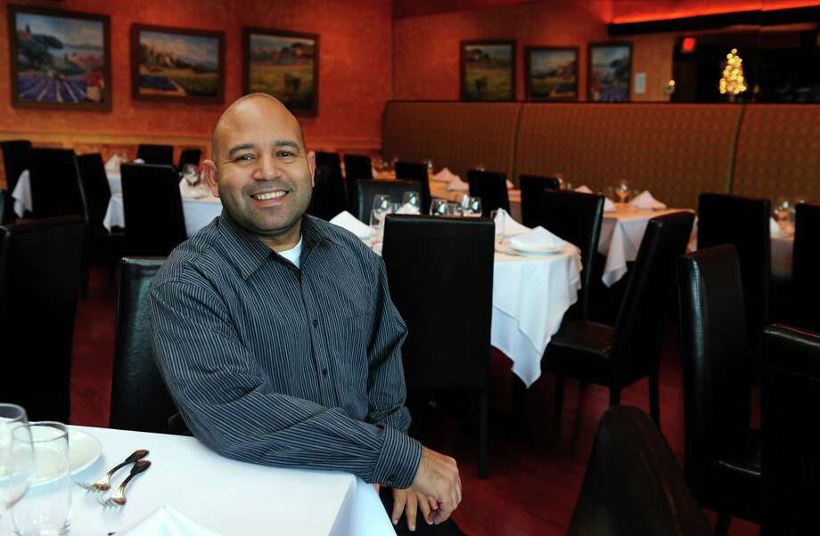 Owner Juan Ceballos sits in the dining room at Arezzo Ristorante on Riverside Avenue in Westport, Conn. Photo: Autumn Driscoll / Connecticut Post