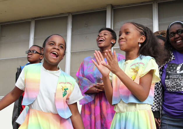Kalea Reed, 8, and Alia Fanagan, 9, members of the Vessels of Honor praise dance group dance before the start of the Martin Luther King Jr. March. Photo: Bria Webb, San Antonio Express-News / ©2013 San Antonio Express-News