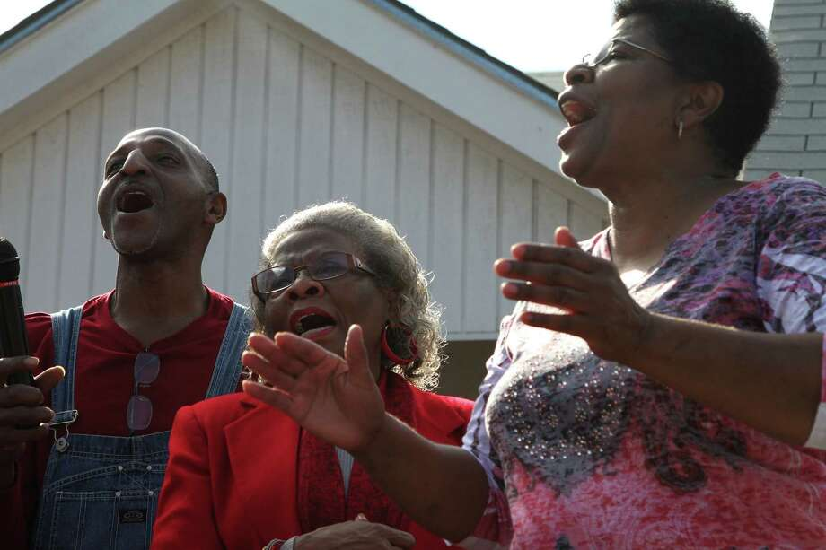 Members of Trinity Missionary Baptist Church sing gospel music as the Martin Luther King Jr. March passes by. Photo: Bria Webb, San Antonio Express-News / ©2013 San Antonio Express-News