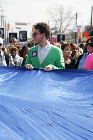 Brad Dusing holds on to the equality flag during the Martin Luther King Jr. March.Kalea Reed, 8, and Alia Fanagan, 9, members of the Vessels of Honor praise dance group dance before the start of the Martin Luther King Jr. March. Photo: Bria Webb, San Antonio Express-News / ©2013 San Antonio Express-News