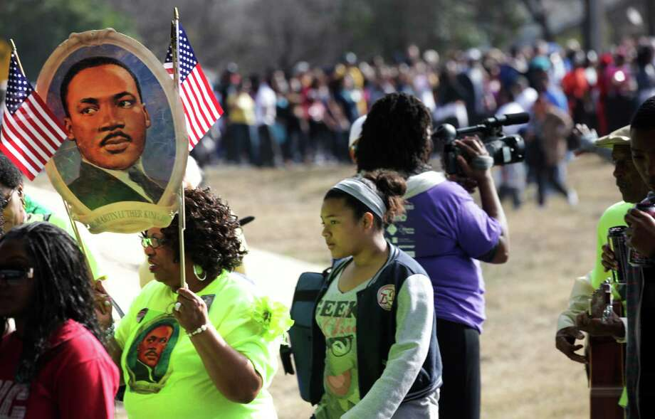 Marchers carry posters of Martin Luther King Jr. during the Martin Luther King, Jr. March along MLK Blvd.  Jan. 21, 2013. Photo: BOB OWEN, San Antonio Express-News / © 2012 San Antonio Express-News