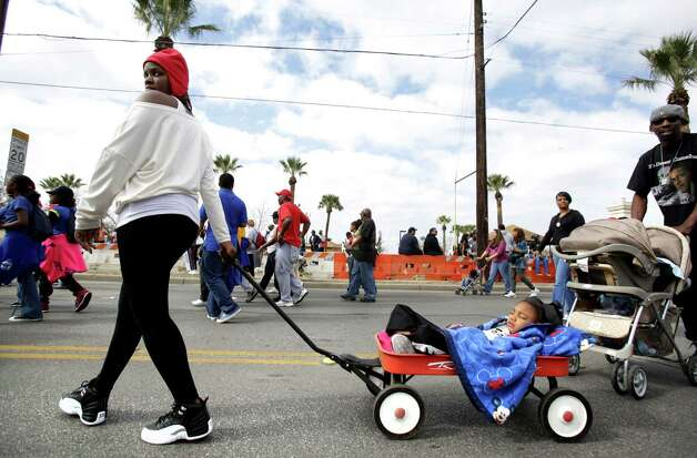 Aramis Parker, left, pulls her neice  Desarae Johnson, 4 yr, in a wagon at the Martin Luther King, Jr. March as they near Pittman-Sullivan Park.  Jan. 21, 2013. Photo: BOB OWEN, San Antonio Express-News / © 2012 San Antonio Express-News