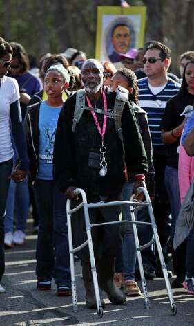 Using a walker to help him, Johnny Shelton walks during the Martin Luther King, Jr. March along MLK Blvd. Shelton walked the entire parade route.  Jan. 21, 2013. Photo: BOB OWEN, San Antonio Express-News / © 2012 San Antonio Express-News