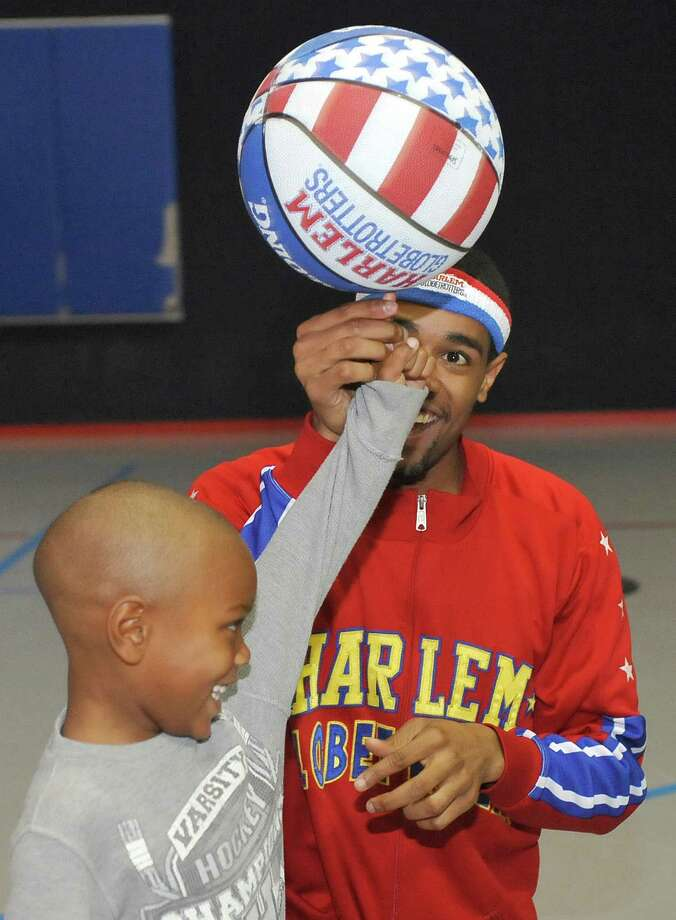 The Harlem Globetrotters' Cheese Chisholm, right, visited the Salvation Army's Boys and Girls Club Monday afternoon at the 2350 IH-10 location.  He talked to all the kids about following their dreams as well as how to deal with bullies. Here, Chisholm, right, helps spin the ball on Taylon White's finger.  The Harlem Globetrotters will be performing Tuesday night, January 21, 2013 at Ford Park.     Dave Ryan/The Enterprise Photo: Dave Ryan