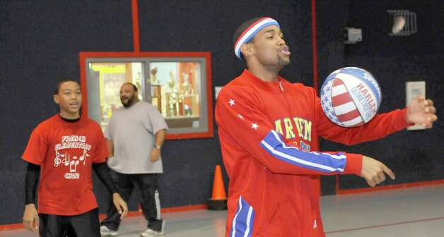 The Harlem Globetrotters' Cheese Chisholm, right, visited the Salvation Army's Boys and Girls Club Monday afternoon at the 2350 IH-10 location.  He talked to all the kids about following their dreams as well as how to deal with bullies. Here, Chisholm demonstrated some of his ball handling techniques for the kids.  The Harlem Globetrotters will be performing Tuesday night, January 21, 2013 at Ford Park.     Dave Ryan/The Enterprise Photo: Dave Ryan