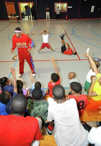 The Harlem Globetrotters' Cheese Chisholm, right, visited the Salvation Army's Boys and Girls Club Monday afternoon at the 2350 IH-10 location.  He talked to all the kids about following their dreams as well as how to deal with bullies. He also did some ball handling drills with the kids.   Here he was picking kids based on what they remembered he had said about living their dreams and not letting anyone tell you otherwise. The Harlem Globetrotters will be performing Tuesday night, January 21, 2013 at Ford Park.     Dave Ryan/The Enterprise