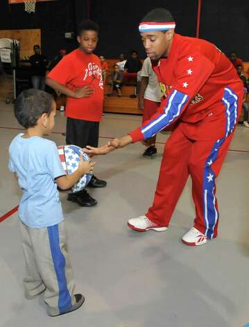 The Harlem Globetrotters' Cheese Chisholm, right, visited the Salvation Army's Boys and Girls Club Monday afternoon at the 2350 IH-10 location.  He talked to all the kids about following their dreams as well as how to deal with bullies. Then he did some ball handling drills with the kids in a big circle.   Here he hands the ball off to 4 year old Durell Smith, left, who held onto it tightly. The Harlem Globetrotters will be performing Tuesday night, January 21, 2013 at Ford Park.     Dave Ryan/The Enterprise Photo: Dave Ryan