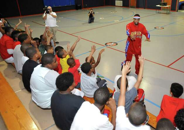 The Harlem Globetrotters' Cheese Chisholm, right, visited the Salvation Army's Boys and Girls Club Monday afternoon at the 2350 IH-10 location.  He talked to all the kids about following their dreams as well as how to deal with bullies. He also did some ball handling drills with the kids.   Here he was picking some volunteers. The Harlem Globetrotters will be performing Tuesday night, January 21, 2013 at Ford Park.     Dave Ryan/The Enterprise Photo: Dave Ryan