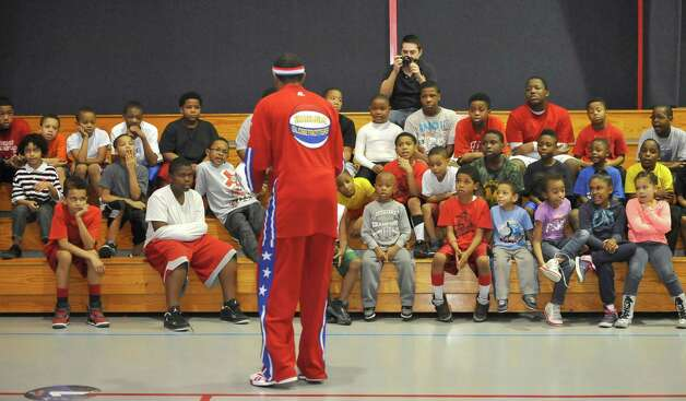 The Harlem Globetrotters' Cheese Chisholm, right, visited the Salvation Army's Boys and Girls Club Monday afternoon at the 2350 IH-10 location.  He talked to all the kids about following their dreams as well as how to deal with bullies. He also did some ball handling drills with the kids.   Here he was telling them what not to do with bullies around. The Harlem Globetrotters will be performing Tuesday night, January 21, 2013 at Ford Park.     Dave Ryan/The Enterprise Photo: Dave Ryan