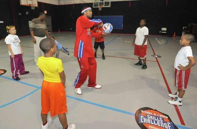 The Harlem Globetrotters' Cheese Chisholm, right, visited the Salvation Army's Boys and Girls Club Monday afternoon at the 2350 IH-10 location.  He talked to all the kids about following their dreams as well as how to deal with bullies. Then he  did some ball handling drills with the kids in a big circle.   Here he was picking kids based on what they remembered he had said about living their dreams and not letting anyone tell you otherwise. The Harlem Globetrotters will be performing Tuesday night, January 21, 2013 at Ford Park.     Dave Ryan/The Enterprise Photo: Dave Ryan