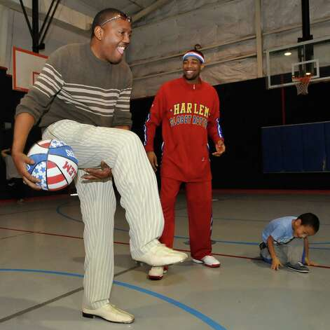 The Harlem Globetrotters' Cheese Chisholm, right, visited the Salvation Army's Boys and Girls Club Monday afternoon at the 2350 IH-10 location.  He talked to all the kids about following their dreams as well as how to deal with bullies. Director David Smith, left, tries to repeat the moves he had just watched Cheese Chisholm, right, do as part of a demonstration.  The Harlem Globetrotters will be performing Tuesday night, January 21, 2013 at Ford Park.     Dave Ryan/The Enterprise Photo: Dave Ryan