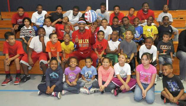 The Harlem Globetrotters' Cheese Chisholm, right, visited the Salvation Army's Boys and Girls Club Monday afternoon at the 2350 IH-10 location.  He talked to all the kids about following their dreams as well as how to deal with bullies. Here, Chisholm, center, poses for a group portrait with all the kids before he had to leave. The Harlem Globetrotters will be performing Tuesday night, January 21, 2013 at Ford Park.     Dave Ryan/The Enterprise Photo: Dave Ryan