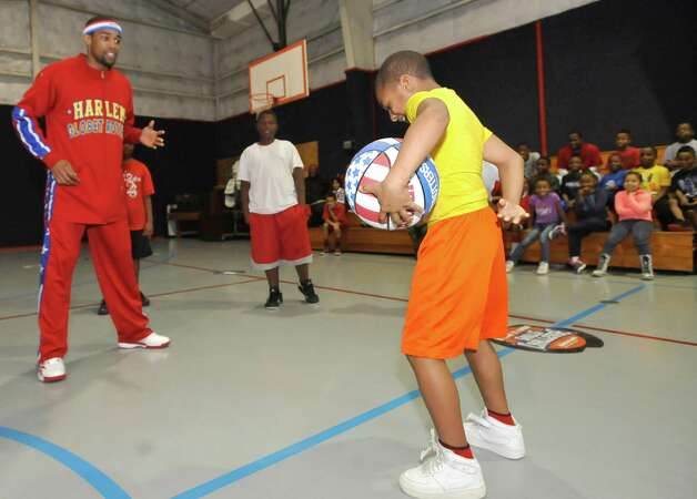 The Harlem Globetrotters' Cheese Chisholm, right, visited the Salvation Army's Boys and Girls Club Monday afternoon at the 2350 IH-10 location.  He talked to all the kids about following their dreams as well as how to deal with bullies. Then he did some ball handling drills with the kids in a big circle. Here he watches Jamichael Foxall, right, try to repeat what he had done earlier. The Harlem Globetrotters will be performing Tuesday night, January 21, 2013 at Ford Park.     Dave Ryan/The Enterprise Photo: Dave Ryan