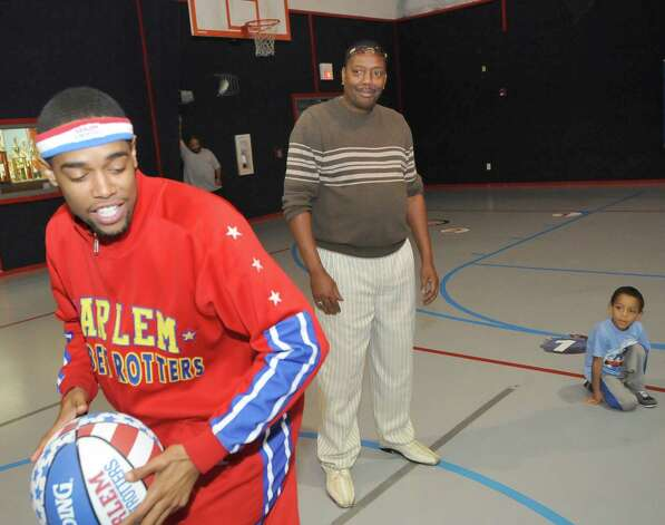 The Harlem Globetrotters' Cheese Chisholm, right, visited the Salvation Army's Boys and Girls Club Monday afternoon at the 2350 IH-10 location.  He talked to all the kids about following their dreams as well as how to deal with bullies. Then he did some ball handling drills with the kids in a big circle.   Director David Smith, right, who was waiting for the ball to be tossed at him,  was also in the circle with his grandson Durell, right. The Harlem Globetrotters will be performing Tuesday night, January 21, 2013 at Ford Park.     Dave Ryan/The Enterprise Photo: Dave Ryan