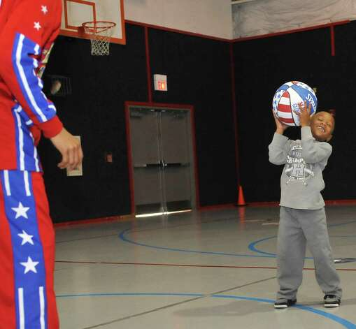 The Harlem Globetrotters' Cheese Chisholm, right, visited the Salvation Army's Boys and Girls Club Monday afternoon at the 2350 IH-10 location.  He talked to all the kids about following their dreams as well as how to deal with bullies. Here, Chisholm throws the ball to Taylon White who knew how to hold onto it. The Harlem Globetrotters will be performing Tuesday night, January 21, 2013 at Ford Park.     Dave Ryan/The Enterprise Photo: Dave Ryan