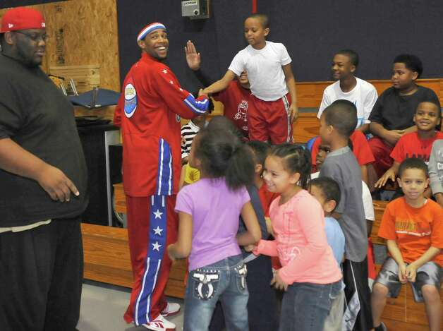 The Harlem Globetrotters' Cheese Chisholm, right, visited the Salvation Army's Boys and Girls Club Monday afternoon at the 2350 IH-10 location.  He talked to all the kids about following their dreams as well as how to deal with bullies. Here, Chisholm, left, high fives with all the kids before he had to leave. The Harlem Globetrotters will be performing Tuesday night, January 21, 2013 at Ford Park.     Dave Ryan/The Enterprise Photo: Dave Ryan