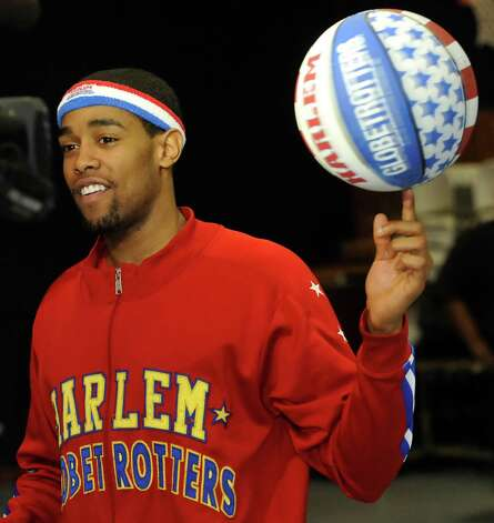 The Harlem Globetrotters' Cheese Chisholm, right, visited the Salvation Army's Boys and Girls Club Monday afternoon at the 2350 IH-10 location.  He talked to all the kids about following their dreams as well as how to deal with bullies. Here, Chisholm demonstrated some of his ball handling techniques for the kids.  The Harlem Globetrotters will be performing Tuesday night, January 21, 2013 at Ford Park.     Dave Ryan/The Enterprise
