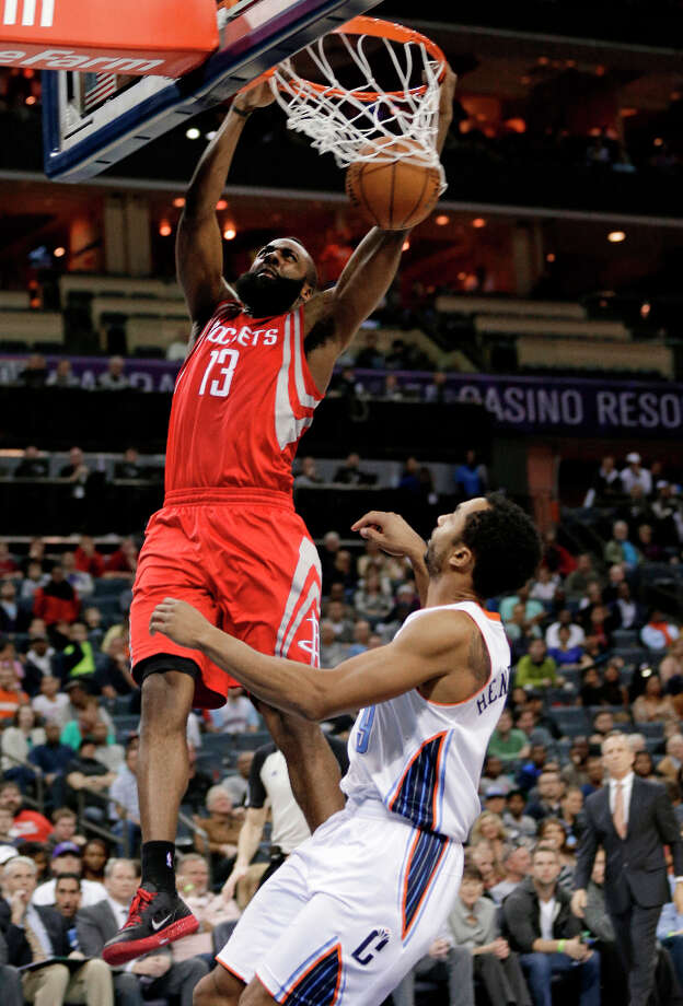 James Harden dunks over Bobcats forward Gerald Henderson (9) during the second half. Harden scored a team-high 29 points. Photo: Chuck Burton, Associated Press / AP