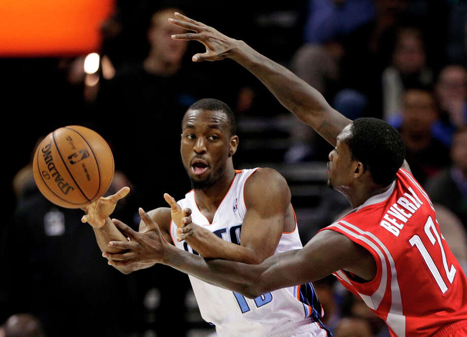 Kemba Walker, left, passes the ball as Patrick Beverley, right, defends during the second half. Photo: Chuck Burton, Associated Press / AP