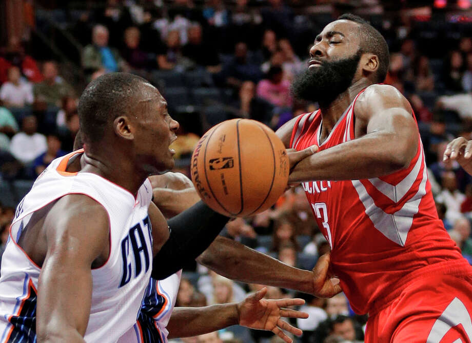 James Harden, right, is fouled by Bismack Biyombo, left, as he drives to the basket during the second half. Photo: Chuck Burton, Associated Press / AP