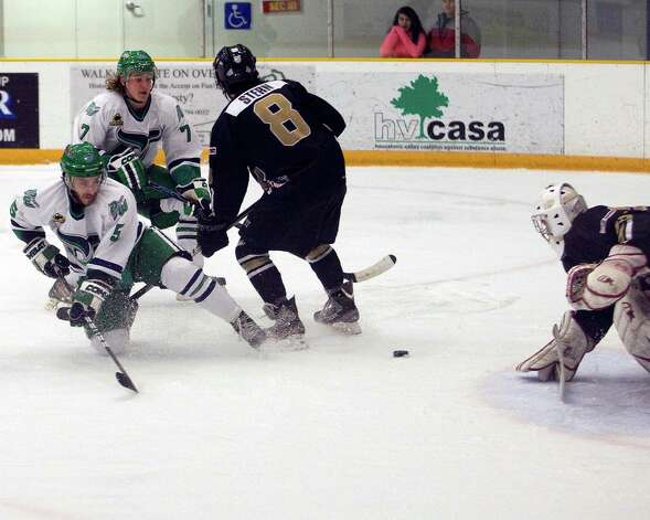 The Whalers' Carlo Ricci (5) goes down on one knee but still manages to get off a shot that is saved by Danville goalie Justin Sand. The Dashers' Ryan Stern tries to keep Danbury's Mike Atkinson from a potential rebound Monday at the Danbury Arena. Photo: Barry Horn / The News-Times Freelance