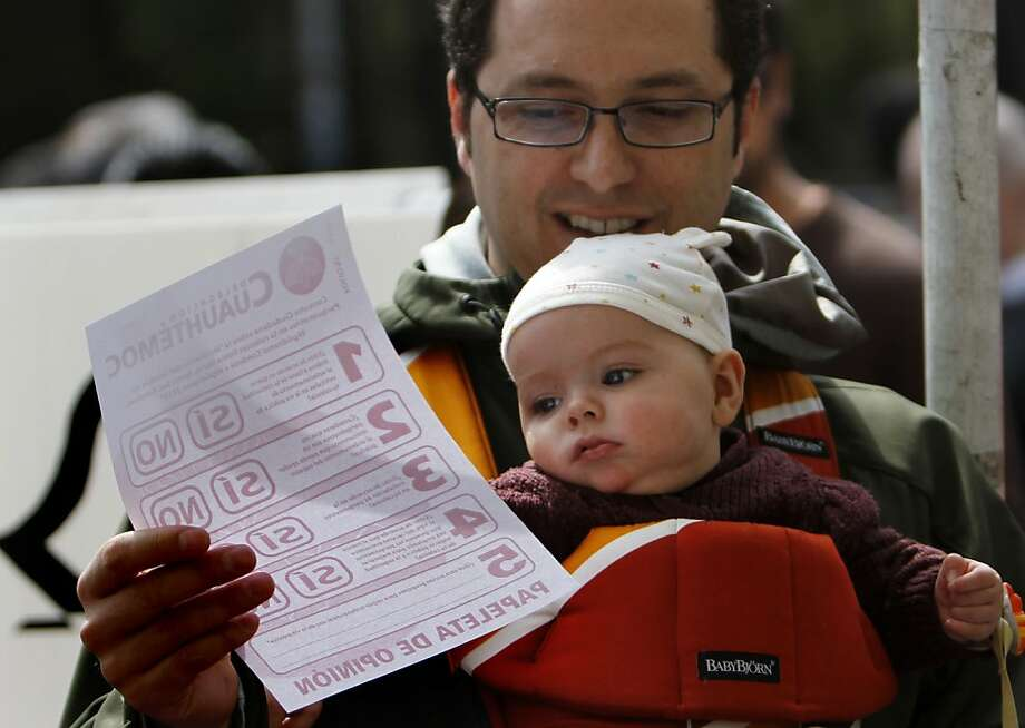 A man carrying a baby holds a ballot during a referendum about the installation of parking meters in the Condesa and Roma neighborhoods in Mexico City, Sunday, Jan. 20, 2013. Authorities are trying to take back the streets by installing parking meters in several well-to-do areas of traffic-choked Mexico City. Many are vehemently opposed, saying the streets are public and no one should profit from them. (AP Photo/Marco Ugarte) Photo: Marco Ugarte, Associated Press