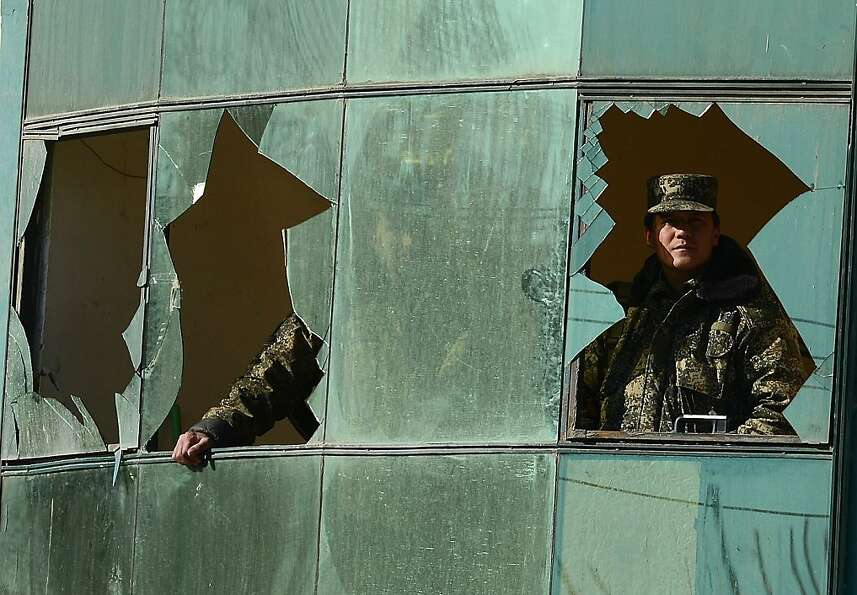 Afghan security force members look out broken windows after the firefight between Afghan forces and