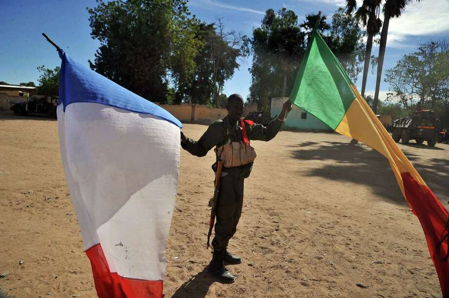 A Malian soldier holds French and Malian flags after arriving in the city of Diabaly on Monday. In addition to Diabaly, the French and Malian troops also occupied the town of Douentza, deserted by Islamist fighters. Photo: ISSOUF SANOGO, Staff / AFP