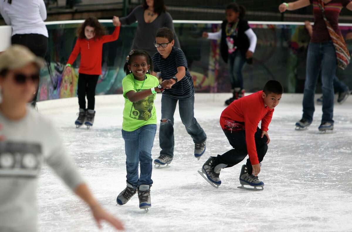 Nine-year-old Julia Bevil, center, skates The ICE at Discovery Green after attending the Martin Luther King Day parade downtown on Monday. The ICE at Discovery Green is open daily through its final day Sunday.