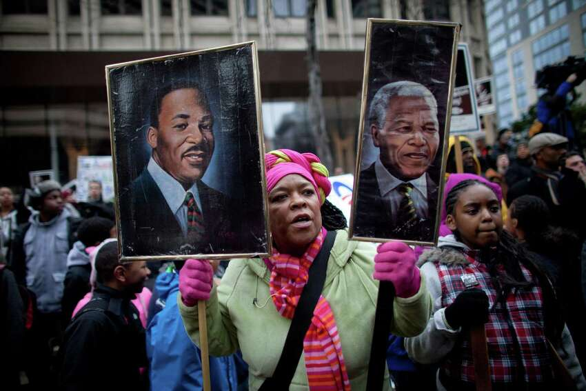 Fai Mathews holds a portrait of Martin Luther King, Jr. and another of Nelson Mandel of South Africa during Seattle's annual march to honor Martin Luther King, Jr. on Monday, January 21, 2013. The federal holiday recognizes the birthday of the civil rights leader.