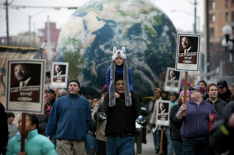 People march as a giant globe is carried by participants during Seattle's annual march to honor Martin Luther King, Jr. on Monday, January 21, 2013. The federal holiday recognizes the birthday of the civil rights leader. Photo: JOSHUA TRUJILLO, SEATTLEPI.COM / SEATTLEPI.COM
