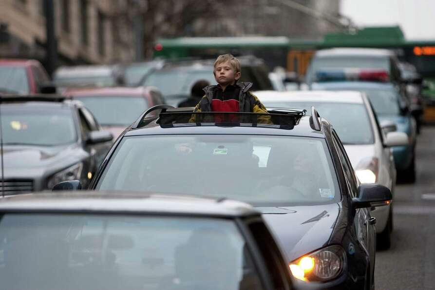 A youngster watches the march from stopped traffic in downtown Seattle during Seattle's annual march