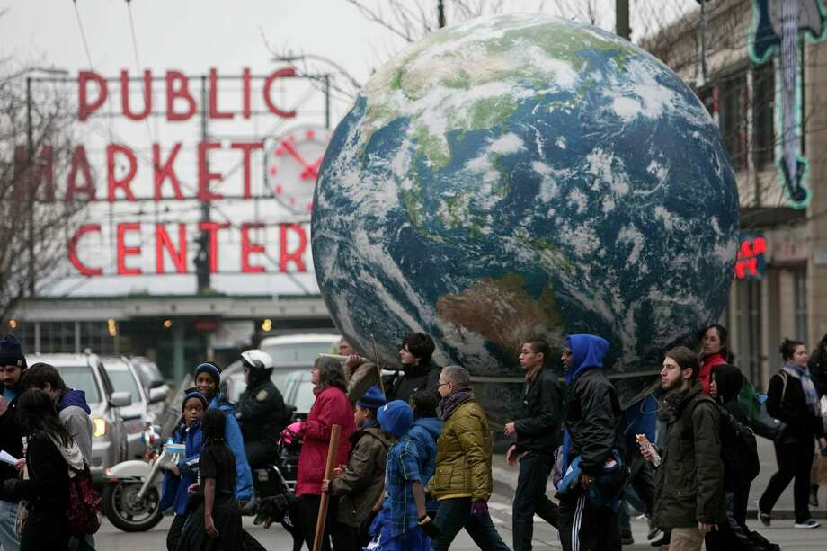 An inflatable globe created by the Backbone Campaign passes Seattle's Pike Place Public Market during Seattle's annual march to honor Martin Luther King, Jr. on Monday, January 21, 2013. The federal holiday recognizes the birthday of the civil rights leader. Photo: JOSHUA TRUJILLO, SEATTLEPI.COM / SEATTLEPI.COM