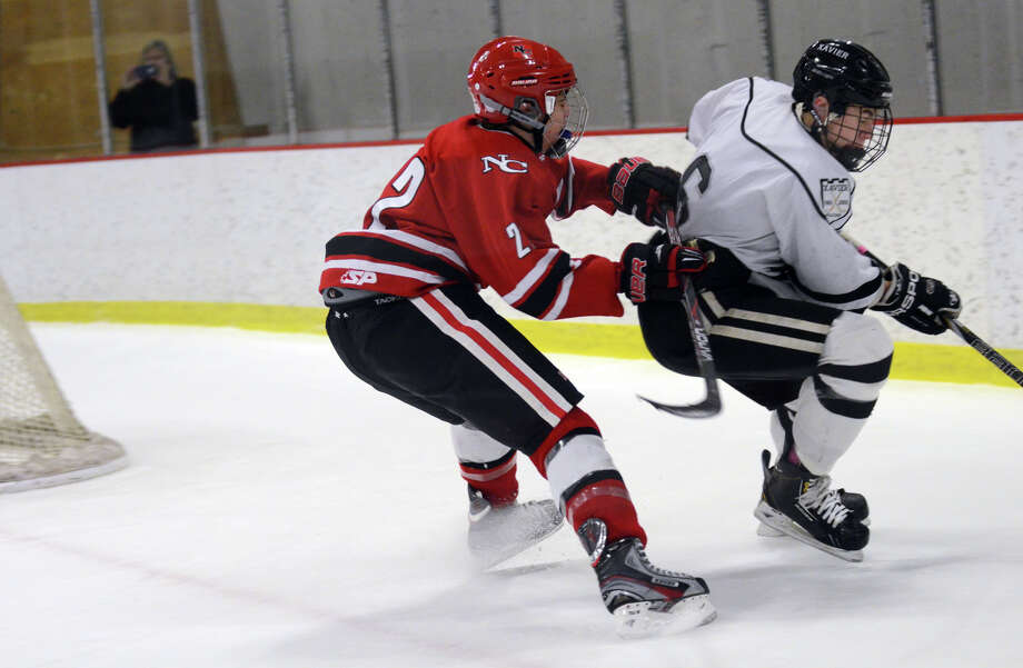 New Canaan's Ryan McMahon (2) checks Xavier's Evan Lindquist (6) during the boys hockey game at the Freeman Athletic Center in Middletown on Monday, Jan. 21, 2013. Photo: Amy Mortensen / Connecticut Post Freelance